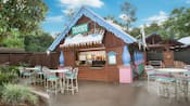 Frostbite Freddy's, a quick-service refreshment hut with patio tables at Disney's Blizzard Beach water park