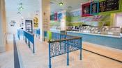 Una heladería con una barandilla de madera y metal en un elaborado diseño para controlar el flujo de los clientes en el área de espera, un congelador y exhibidores a un lado, 2mostradores largos para servir helado con frentes de azulejos y vidrio, y un letrero con un menú colgando del techo