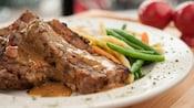 2tranches de pain de viande recouvertes de sauce brune avec des légumes