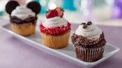 3 cupcakes em uma bandeja, um com orelhas do Mickey