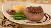 Steak on a plate with green beans, a biscuit, roasted onions and sauce