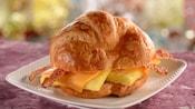 Un sándwich de croissant relleno con tocineta, queso cheddar y huevos revueltos