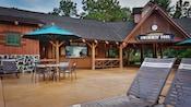 Espreguiçadeiras e mesas com guarda-sol em um pátio em frente ao Meadow Snack Bar