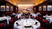 Área de comidas con paneles de madera y un conjunto de mesas largas para la cena en Shula's Steak House