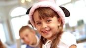 Primer plano de una niña sonriente con un sombrero de orejas de Princesa Minnie