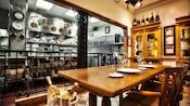 Mesa de madera puesta para 2, frente a una cocina a la vista en Chef's Table en Victoria and Albert's