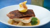 Blackened fish fillet with grilled grit cake, stewed green tomatoes and lemon garnish