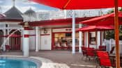 Red-and-white exterior of the Backstretch Pool Bar with patio tables, umbrellas and chairs next to the pool
