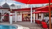 Fachada exterior de color rojo y blanco del Backstretch Pool Bar con mesas en el patio, sombrillas y sillas al lado de la piscina