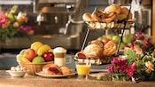 Un vaso de jugo de naranja y una taza de capuccino junto a canastas de frutas, pancitos y pasteles