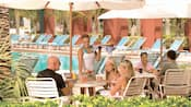 Varias personas sentadas en mesas junto a la piscina
