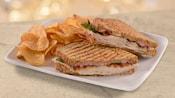 Un sandwich panini dans une assiette avec des croustilles