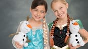 Two young girls dressed as Anna and Elsa hold plush Olaf toys and pose for a studio portrait against a standard backdrop
