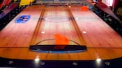 Air hockey arcade game with wooden floor instead of ice