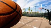 Primer plano en perspectiva de un balón frente a una cancha de baloncesto.