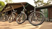 4 bicicletas enfileiradas em frente a um ponto de aluguel