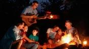 Algunos Huéspedes disfrutan de la música de una guitarra al rededor de una fogata en Disney's Fort Wilderness Resort