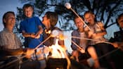 A family roasting marshmallows at a campfire