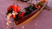 Canoa en una playa de arena decorada con flores tropicales