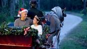 Un papá y su hija disfrutan un momento encantador en un trineo festivo guiado por un Miembro del Elenco de Disney.