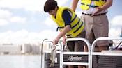 Un huésped joven con un chaleco salvavidas saca una lubina de boca grande recién pescada del agua mientras su padre lo observa