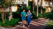 Um homem e uma mulher fazendo cooper por um caminho de um Hotel Resort Disney.