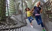 Duas visitantes dando risadas ao passarem pela área de recreação no Clube da Disney