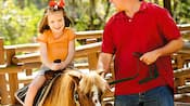A little girl enjoying a pony ride as her father holds the reigns