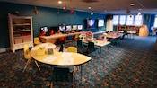 Um centro de recreação para crianças com temática náutica, com mesas de artesanato, e 2 TVs de tela plana