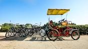 Um bicicletário com 6 bicicletas e uma bicicleta de quatro rodas