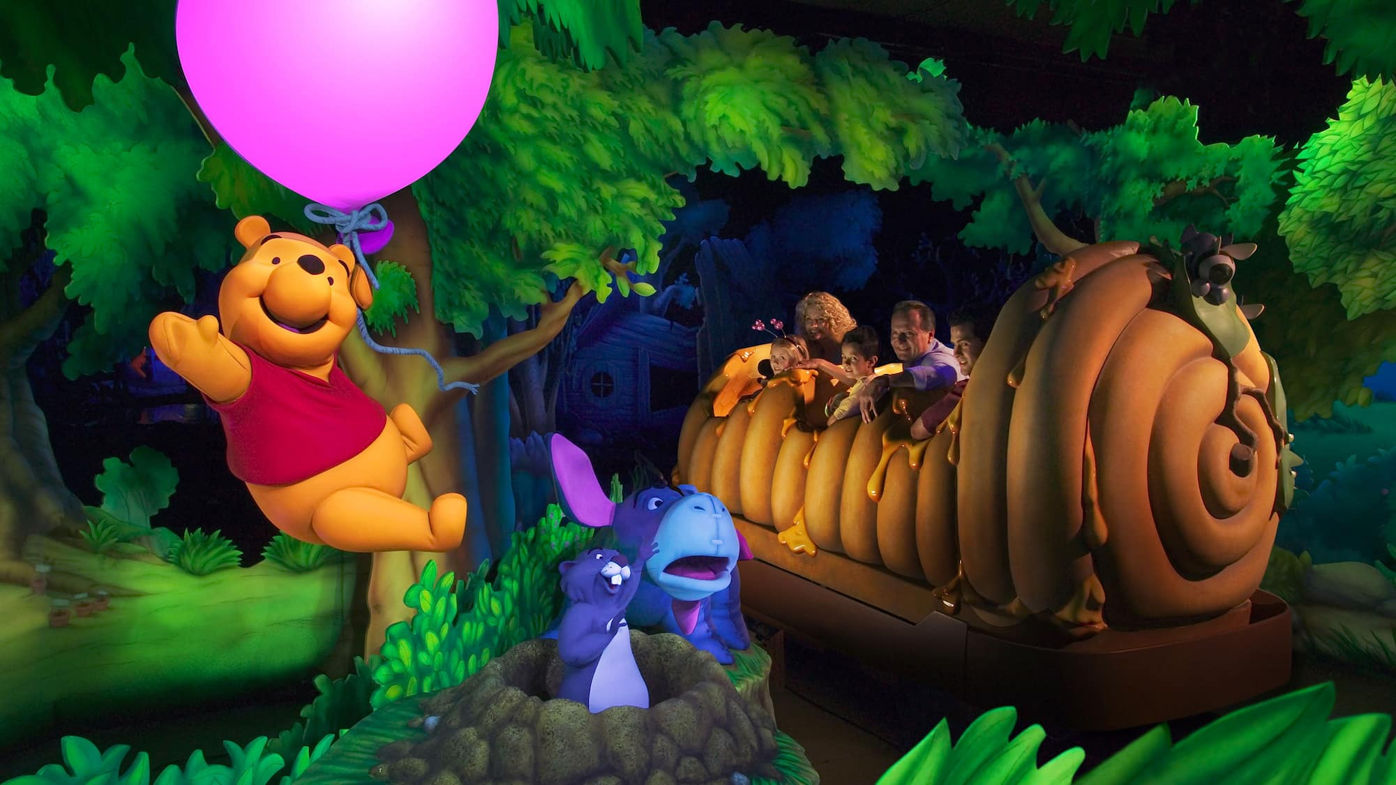 Pooh Bear floats with a balloon above Eeyore and Gopher while Guests travel in a giant honey pot
