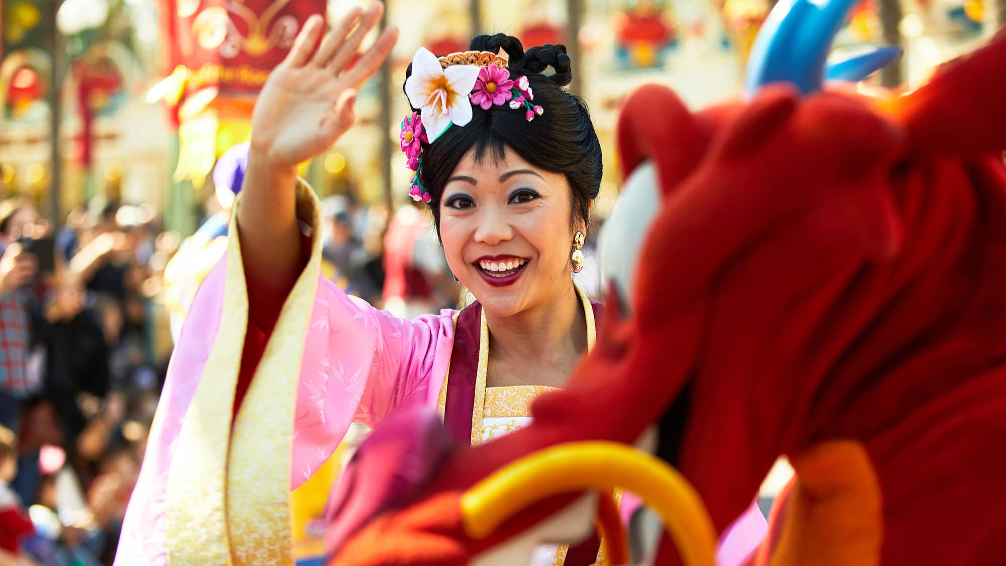 Mulan stands next to Mushu and waves to Guests