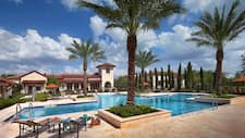Luxurious outdoor pool framed with with palm trees and cypress trees at Golden Oak Clubhouse