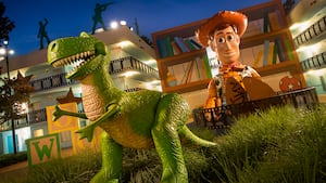 The illuminated exterior of Disney's All Star Movies Resort featuring large statues of T Rex and Woody