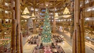 Un árbol de Navidad alto en medio de un gran lobby de hotel rústico con un diseño de techo abierto