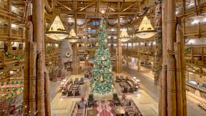 A tall Christmas tree in the middle of a large, rustic style hotel lobby with an open ceiling design