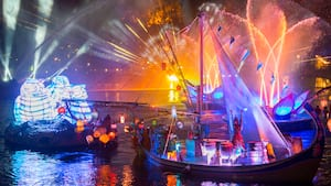 Several decorated boats floating on a lake at night, illuminated by colorful lights and lasers