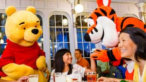 Winnie the Pooh and Tigger greet 2 women dining at The Crystal Palace