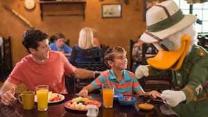 Donald Duck greets a boy dining with his father at Tusker House Restaurant