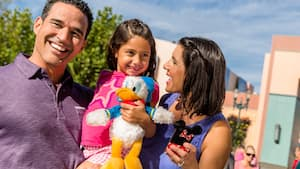 A man, woman and their daughter smiling as they enjoy Disney's Hollywood Studios