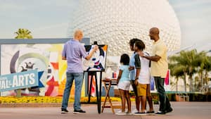 An artist paints Mickey Mouse in front of Spaceship Earth as a family looks on