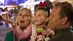 A young Guest holds her hand out to catch a snowflake while her parents look on