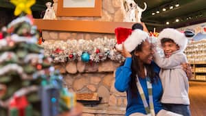 A mother and son wearing Santa hats in a store decorated with a holiday wreath and a Christmas tree