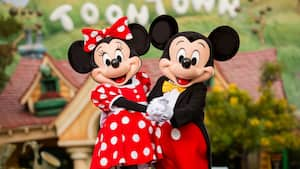 Mickey Mouse and Minnie Mouse clasp hands and dance at Toontown