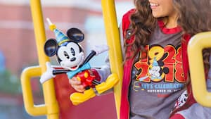 A Guest shows off a Mickey Mouse birthday figurine