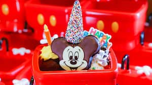 A Mickey Mouse themed candy topped with a wizard hat made of sprinkles, served in a plastic wagon