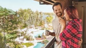 Una pareja sonriente con tazas en mano en un balcón sobre el área de la piscina