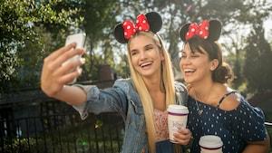 2mujeres sonrientes con vasos en mano se toman una selfi