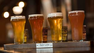 A flight of 4 beers on a board with a sign that reads Baseline Tap House