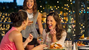 3 women drink and laugh in a restaurant seating area